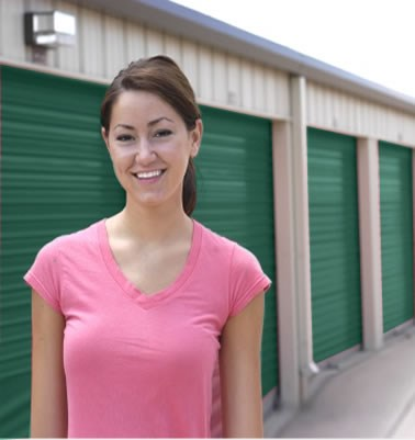 A Smiling Woman Stands In Front Of A Self Storage Facility